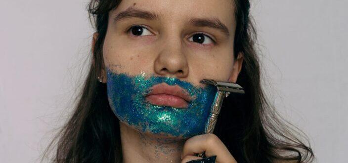 Girl shaving her mustache made of glitters.