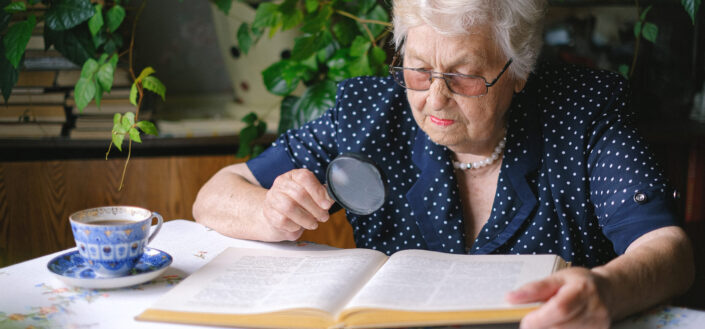 Old lady reading with a magnifying glass