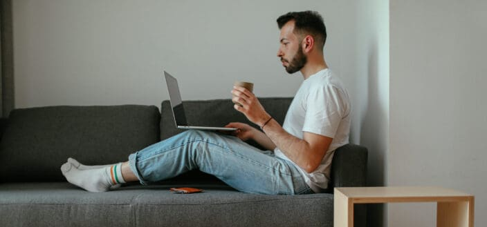 A man sitting on his couch while working