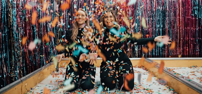 two women playing with confetti while kneeling
