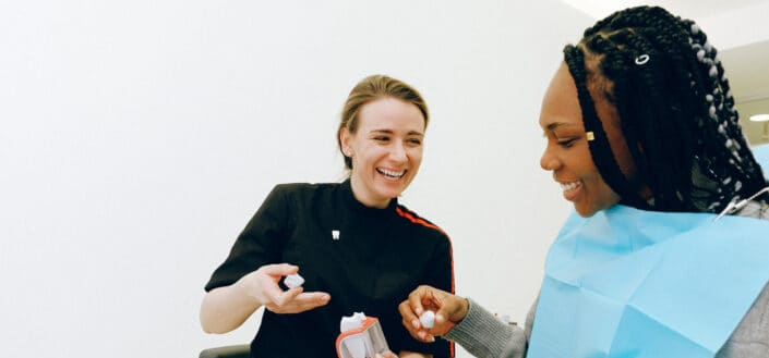cheerful dentist discussing tooth structure to her patient