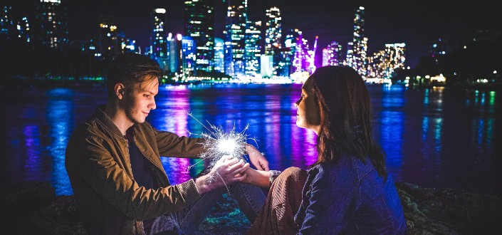 man and woman holding sparkler near river