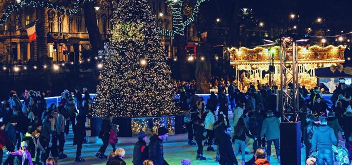 people skating around a christmas tree