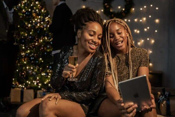two women smiling in front of an iPad