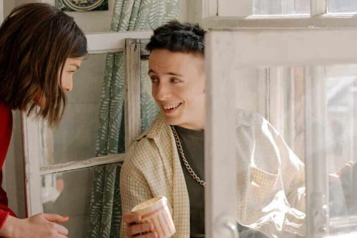 woman smiling at a smiling man sitting on a window ledge holding a cup