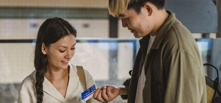 a woman and a man smiling at a coupon that the man is holding