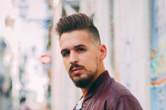 man in brown leather jacket standing near wall