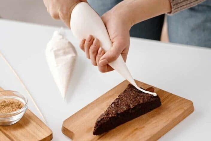 hand piping frosting into a slice of chocolate cake