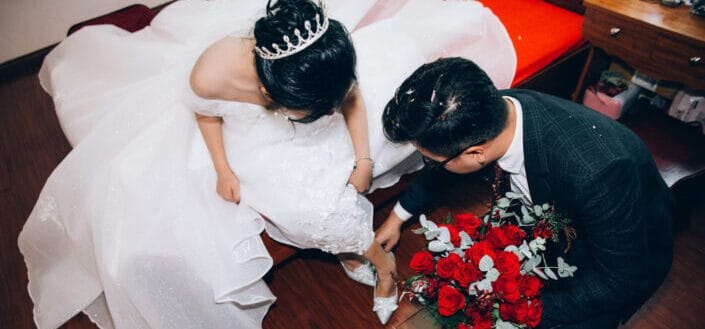 groom fixing the shoe of bride