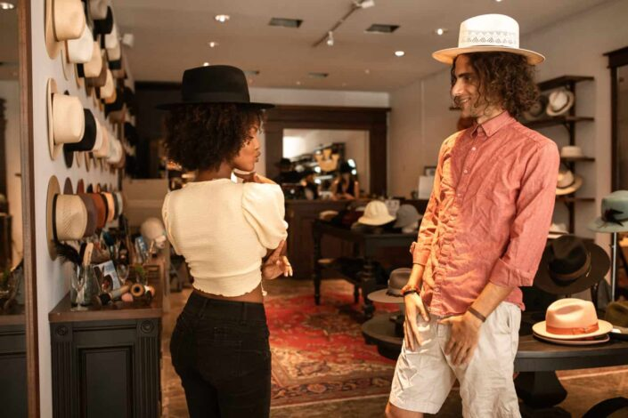 man and woman trying on hats on a boutique