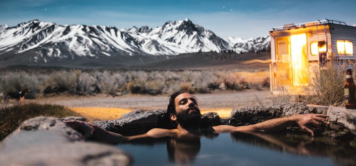 man taking a bath under bright stars and mountains in the background