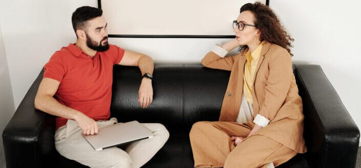 two office workers talking in a sofa