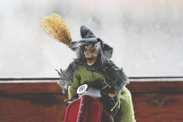Old witch rag doll on a motorcycle