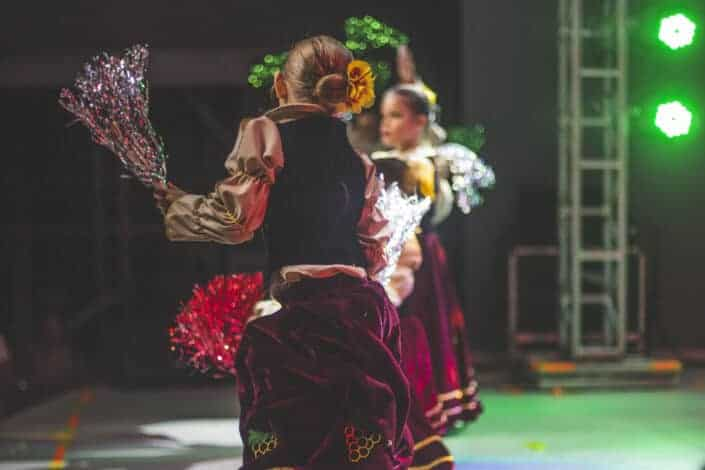 Girls dancing on a stage with flowers on hand