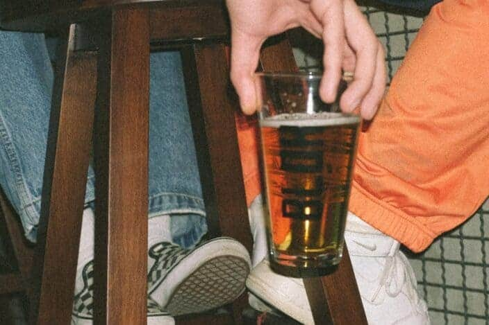 Guy holding a glass of beer.