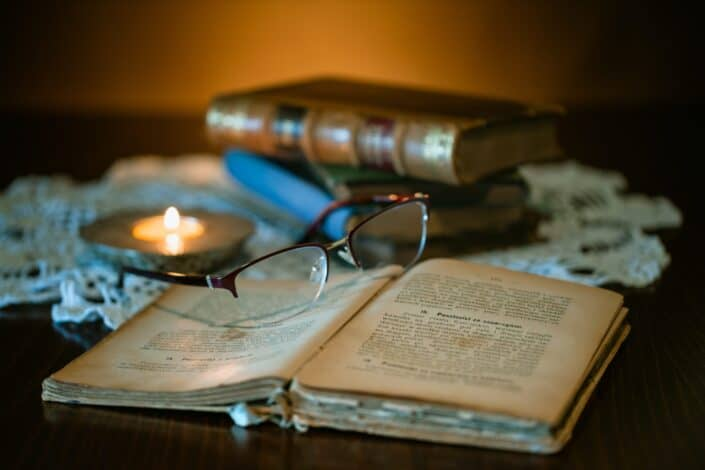 Open book with pair of glasses on top