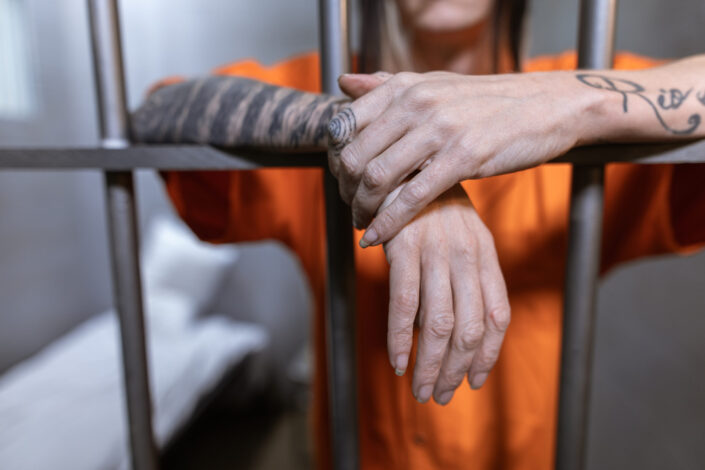 Man standing behind prison bars