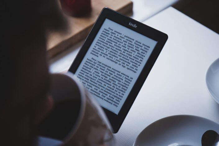silhouette of a man drinking coffee while looking at his tablet