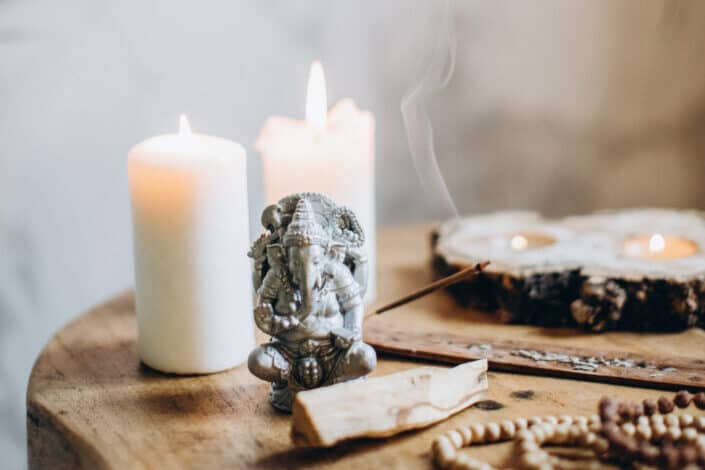 lighted candles, woods, and a metal elephant on table top