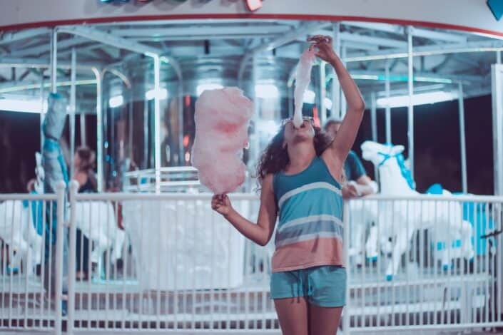 A person eating a large cotton candy in front of a carousel