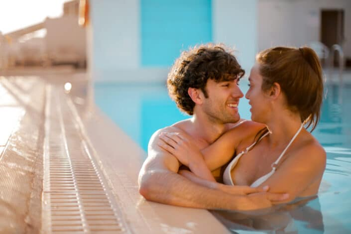 Couple, staring and hugging on a pool.