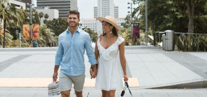 Couple holding hands and walking the dog