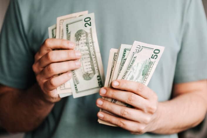 Crop man counting dollar bills