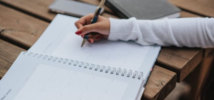 hand of a woman about to write something in a calendar