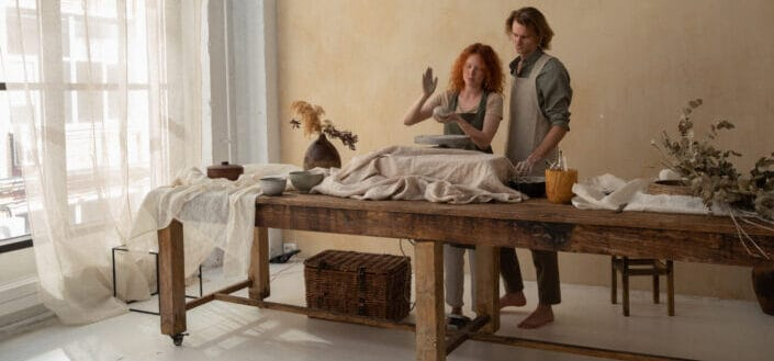 man and woman behind a table doing pottery