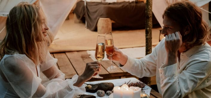man and woman toasting wine in a rustic venue