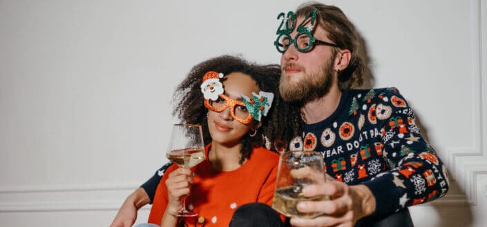 man and woman sitting closely while wearing festive outfits and statement eyeglasses