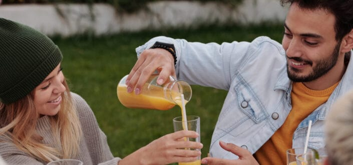 man pouring juice from a pitcher to a woman glass