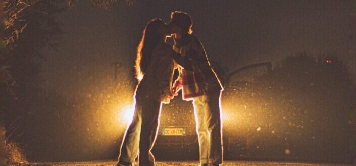 couple kissing in front of a car illuminated by car headlights at night