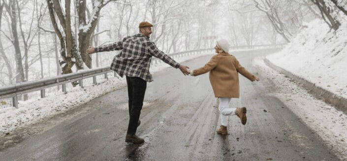 man and woman holding hands in the middle of a snowy street