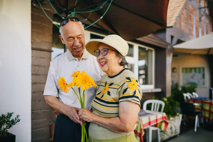 an old couple holding each other while the woman is holding flowers