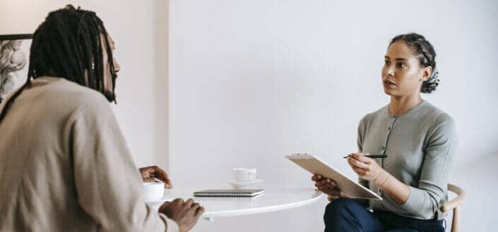 Ethnic female psychotherapist listening to black clients explanation