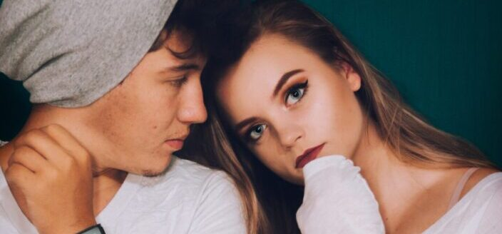 Guy staring at his girl, leaning on his shoulder.