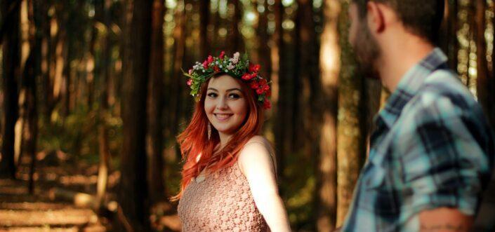 Girl in flower headdress, smiling towards her guy.
