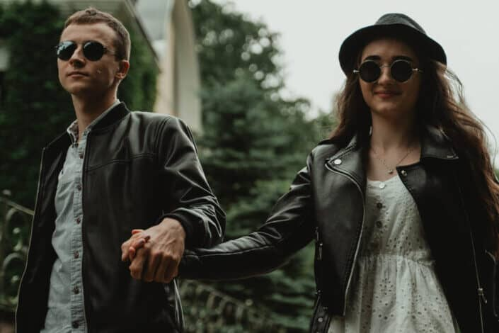 Couple on sunglasses, holding hands while walking.