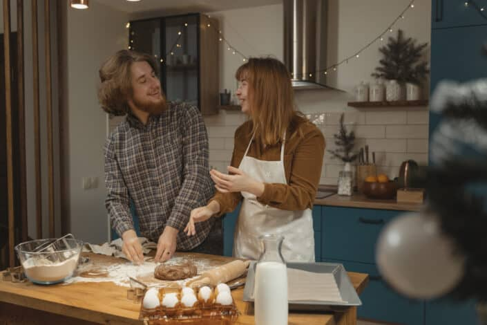 Couple having fun kneading some dough together.