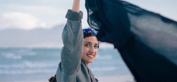 Happy woman keeping up black shawl in wind