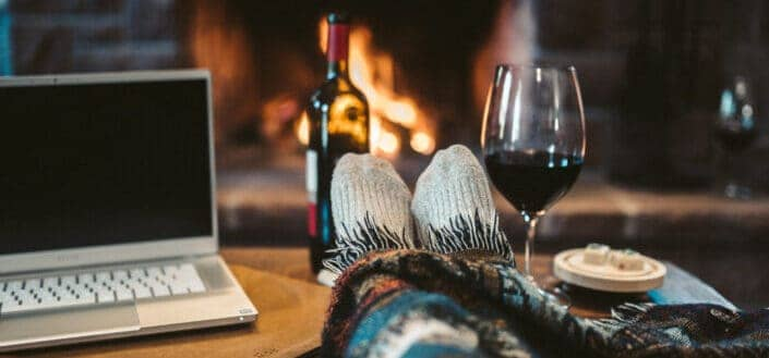 laptop beside wine glass on brown wooden table