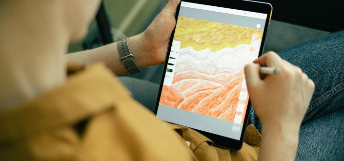 man drawing an art on his tablet