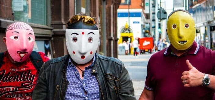 Three guys wearing a mask on the street.