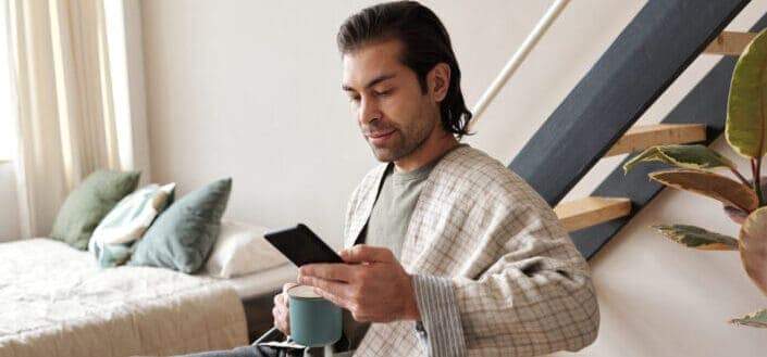 Man looking at his cellphone while having coffee