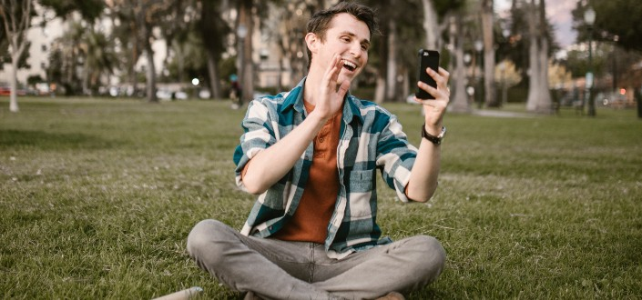 man smiling while waving his hand in front of his phone