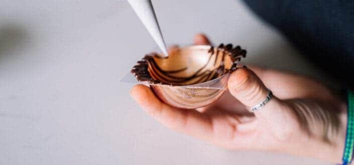 A hand decorating dessert