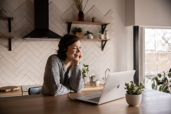 a woman laughing in front of her laptop