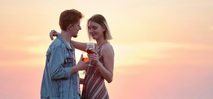 couple holding each other while holding wine glasses