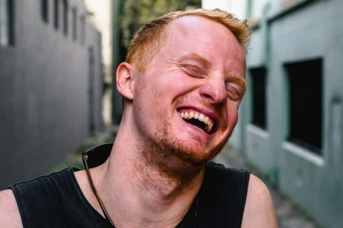 man laughing in an alley
